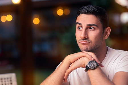 sense of space: Surprised Young Man Sitting in a Restaurant Stock Photo