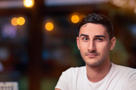 expressive mood: Surprised Young Man Sitting in a Restaurant Stock Photo