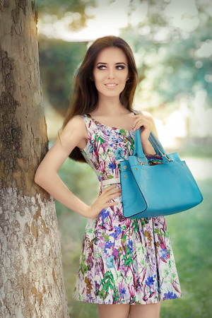 Woman in Floral Dress Holding Stylish Purse