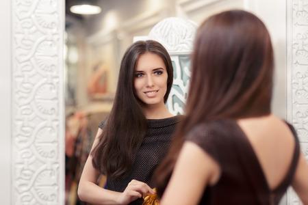 espejo: Muchacha Hermosa Mirada en el espejo y El intentar en un elegante vestido Foto de archivo