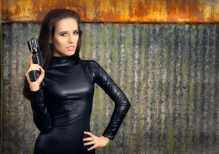 mujer con arma: Agente Mujer esp�a de Negro traje de cuero de la explotaci�n agr�cola del arma Foto de archivo