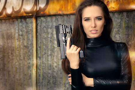 holding gun: Spy Agent Woman in Black Leather Suit Holding Gun