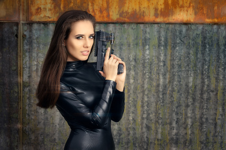 spy girl: Spy Agent Woman in Black Leather Suit Holding Gun