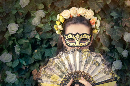 white party: Beautiful Woman with Floral Wreath, Mask and Fan Stock Photo