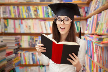 bookish: Surprised School Student Reading a Book in a Library Stock Photo