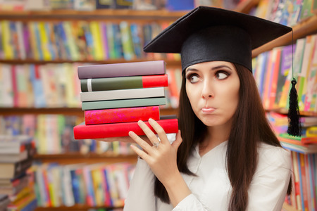 bookish: Funny  Student with Graduation Cap Holding Books Stock Photo