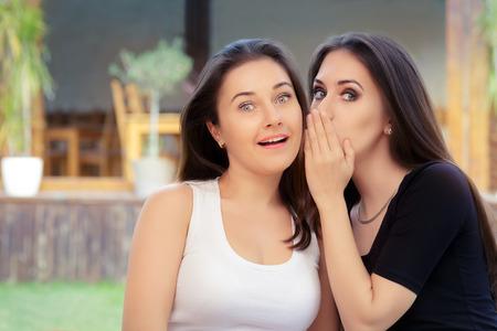 Two Best Friend Girls Whispering a Secret