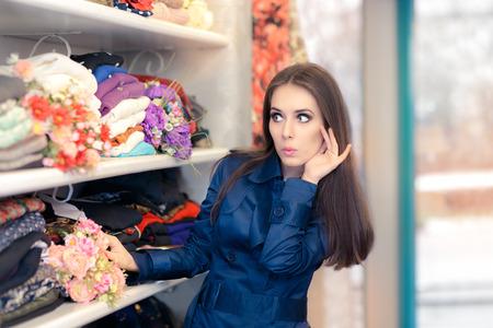 mujer pensando: Chica sorprendida en azul Trench Coat Compras Foto de archivo