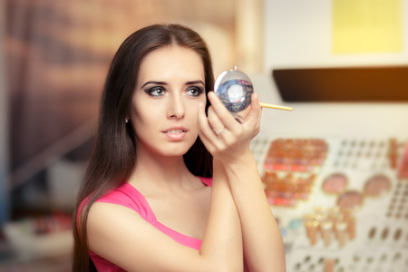 Beautiful Woman with Make-up Brush Looking in a Mirror Banque d'images