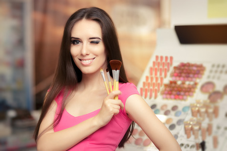 mujer maquillandose: Mujer feliz que sostiene un pincel de maquillaje Foto de archivo
