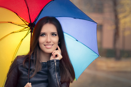 Happy Autumn Woman Holding Rainbow Umbrella out in the Rain