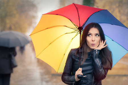 is raining: Surprised Autumn Woman Holding Rainbow Umbrella Stock Photo
