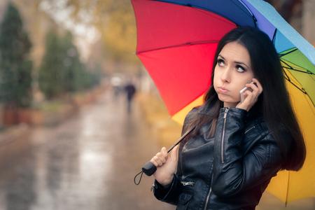 raining: Muchacha del otoño con un paraguas del arco iris y un Smartphone