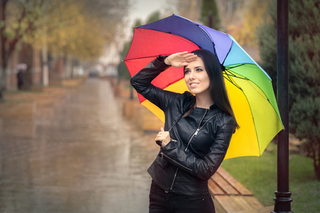 out in town: Happy Autumn Woman Holding Rainbow Umbrella Checking for Rain