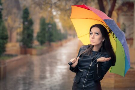 expressive: Surprised Autumn Woman Holding Rainbow Umbrella Stock Photo