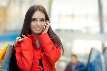 answering call: Shopping Mall Girl in a Red Coat Talking on Smartphone Stock Photo