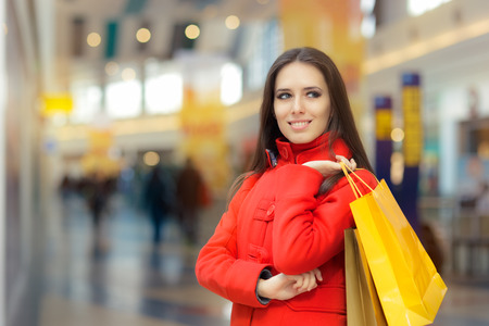 spender: Happy Girl in a Red Coat Shopping in a Mall Stock Photo