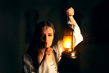 finger on lips: Medieval Princess Holding Lantern and Keeping a Secret Stock Photo