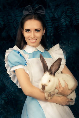 Chica disfrazados de Alicia en el país de las maravillas con el conejo blanco Foto de archivo - 46527404
