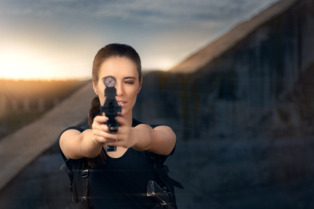 tough girl: Powerful Woman Aiming Gun Action Movie Style Stock Photo