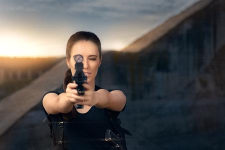 pointing gun: Powerful Woman Aiming Gun Action Movie Style Stock Photo
