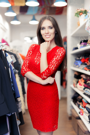 christmas spending: Woman wearing red lace dress in fashion store Stock Photo