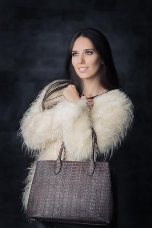 fur: Beautiful Winter Woman in Fur Coat with Bag