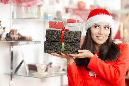 christmas spending: Christmas Girl Holding Presents in Gift Shop