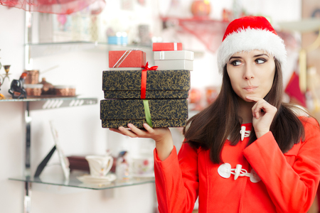christmas spending: Curious Christmas Girl with Presents in Gift Shop Stock Photo