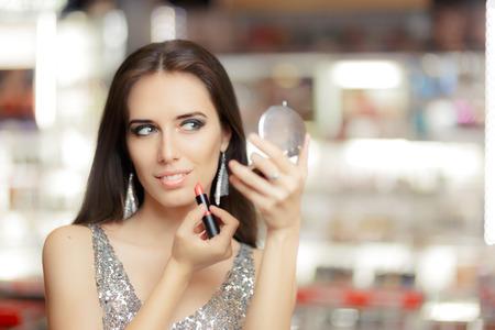Glamour mujer con el lápiz labial y el espejo de maquillaje Foto de archivo