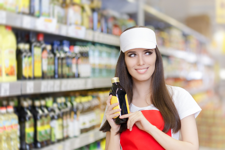 Smiling Supermarket Employee Holding a Product