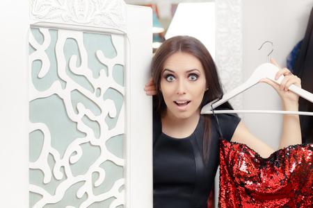 sorprendido: Asombrado chica intentar en rojo vestido de fiesta en Vestidor Foto de archivo