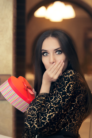 fashion clothing: Surprised Beautiful Woman Holding Heart Shape Gift