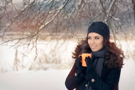 black hat: Winter Woman Holding a Hot Drink Mug Stock Photo
