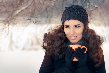 knit cap: Winter Woman Holding a Hot Drink Mug Stock Photo