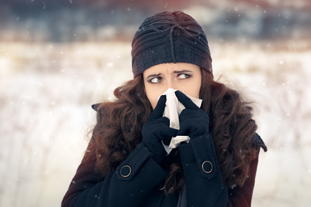 running nose: Woman with Tissue Outside Feeling Bad Cold Winter