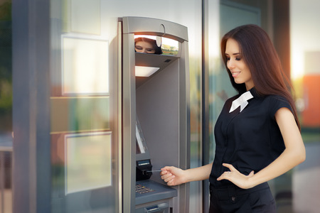 black money: Woman with Credit Card at ATM cash machine Stock Photo