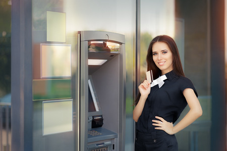 automatic teller machine: Woman with Credit Card at ATM cash machine Stock Photo