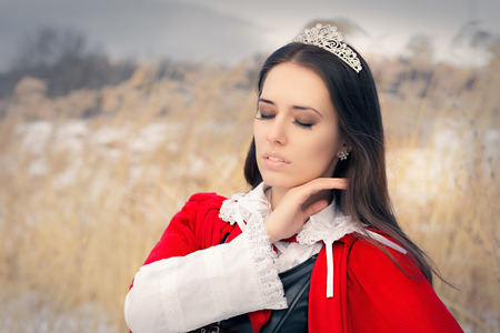 regal: Princess Wearing Tiara and Red Cape Outside Stock Photo