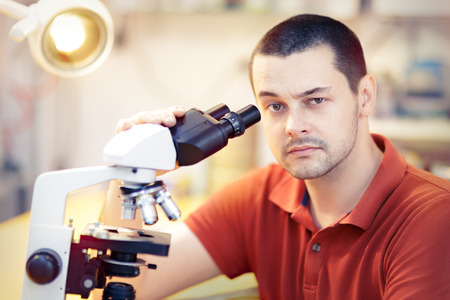 skeptical: Skeptical Young Male Researcher with microscope Stock Photo