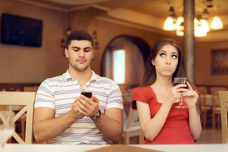 obsessed: Bored Girl in a Date with Her Boyfriend Obsessed with his Smartphone Stock Photo