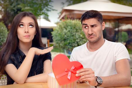 caras graciosas: Muchacha que rechaza el regalo en forma de coraz�n de su novio Foto de archivo