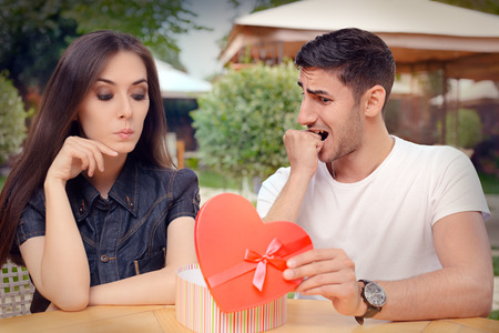 timorous: Nervous Boyfriend presenting his Gift to his Picky Girlfriend Stock Photo