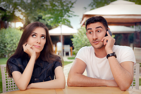 Girl Feeling Bored while her Boyfriend is on The Phone Banque d'images