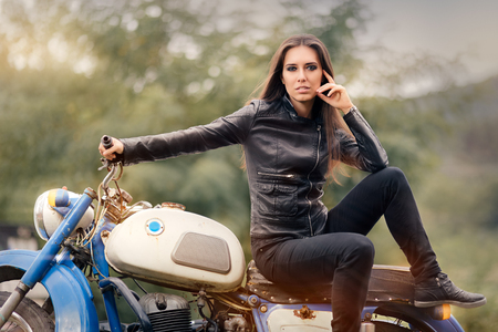 Biker Girl in Leather Jacket on Retro Motorcycle Фото со стока - 52509529