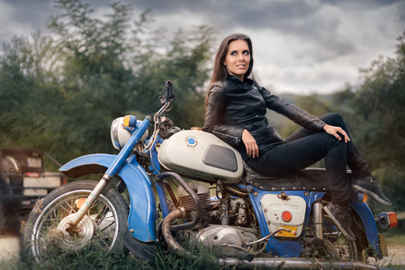 shoes off: Biker Girl in Leather Jacket on Retro Motorcycle