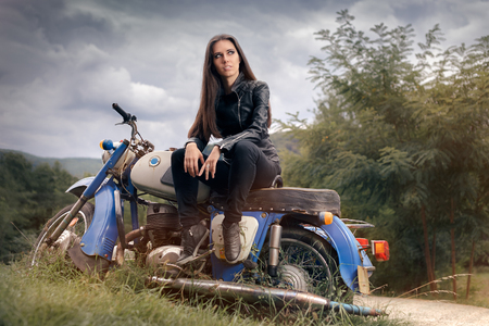 tough woman: Biker Girl in Leather Jacket on Retro Motorcycle