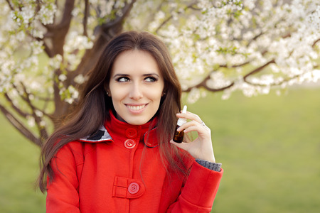 nasal drops: Smiling Woman with Respiratory Spray  in Spring Blooming Decor