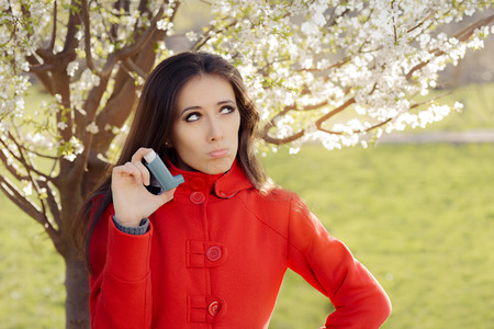 inhale: Upset  Woman with Inhaler  in Spring Blooming Decor