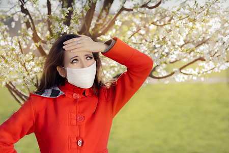 with pollen: Woman with Allergy with Respirator Mask in Spring Blooming Decor